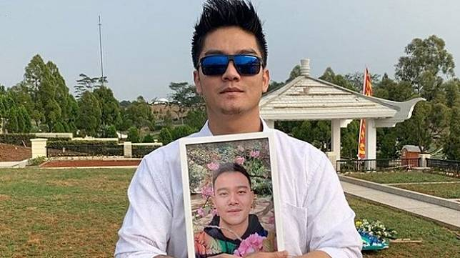 Boy William di pemakaman sambil memeluk foto sang adik, Raymond Hartanto. [Instagram]