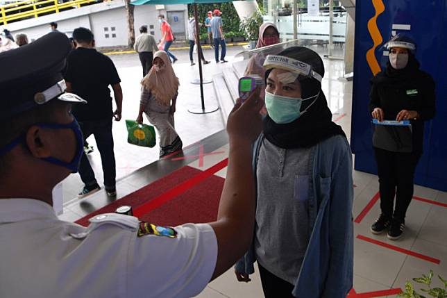 A security guard checks the body temperature of a visitor in front of the World Trade Center shopping mall in Surabaya, East Java on May 21 as the city implements large-scale social restrictions (PSBB). Indonesia's economy may shrink 3.5 percent this year should the PSBB last for four months, according to a worst-case projection by the World Bank.