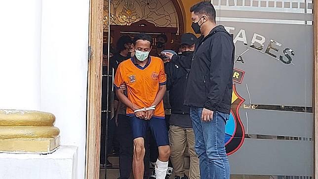 Pelaku pembunuhan digelandang polisi dengan luka tembak di kaki, Jumat (11/6/2021). (Foto: Sindonews/Lukman Hakim).
