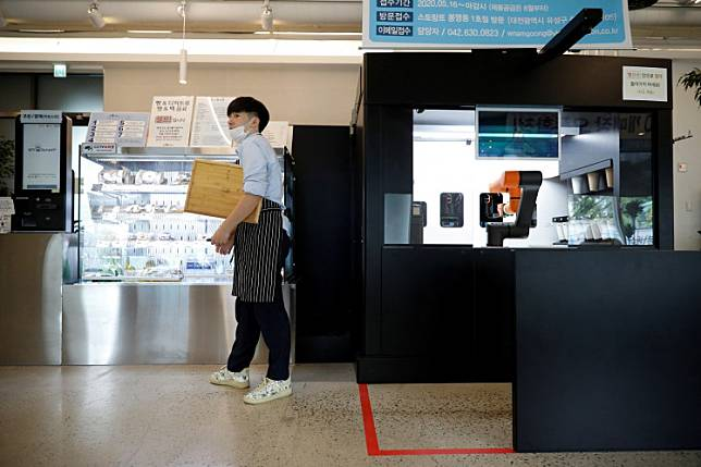 An employee stands next to a barista robot that takes orders, makes coffee and brings the drinks straight to customers in Daejeon, South Korea, May 25, 2020.