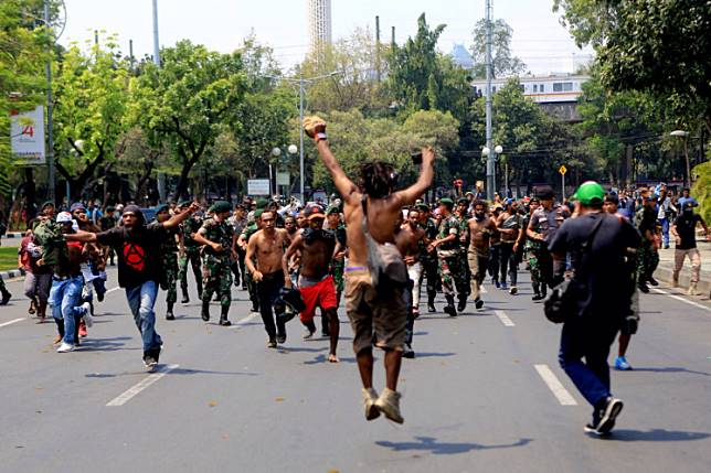 Aggrieved: Escorted by military personnel and police officers, Papuans demonstrate in front of the Presidential Palace in Central Jakarta on Thursday. Protesters called on the government to take seriously cases of physical and racial abuse against Papuan students by security personnel in Surabaya, East Java, on Saturday.