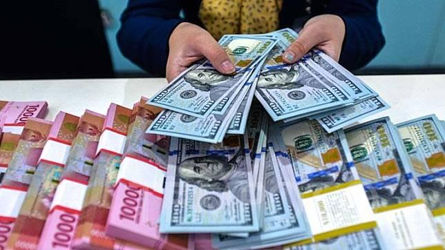 Karyawan bank mengitung uang 100 dolar amerika di Bank Mandiri Pusat, Jakarta, Selasa, 17 Maret 2020. Nilai tukar (kurs) rupiah yang ditransaksikan antarbank di Jakarta pada Selasa, semakin tertekan dampak wabah COVID-19. Rupiah ditutup melemah 240 poin atau 1,61 persen menjadi Rp15.173 per dolar AS dari sebelumnya Rp14.933 per dolar AS. TEMPO/Tony Hartawan