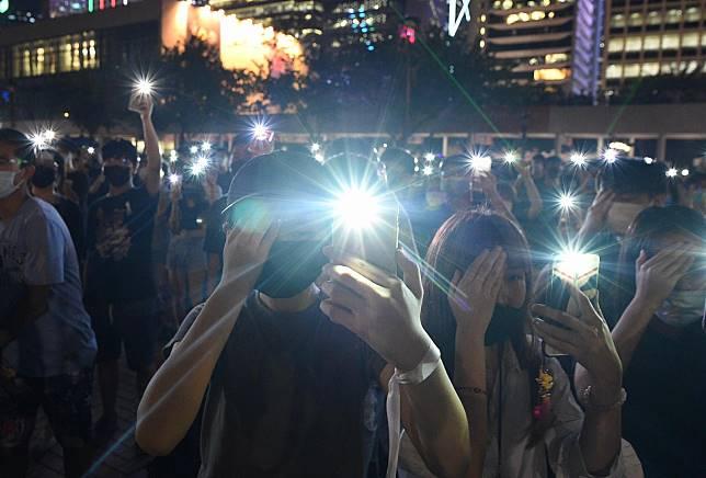 集會人士遮掩右眼,紀念右眼受傷女示威者。