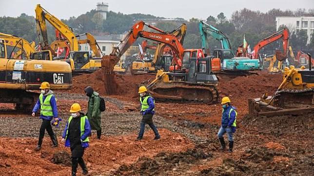 Para pekerja dan alat berat di lokasi pembanguan rumah sakit di Kota Wuhan, China. [Foto/AFP]
