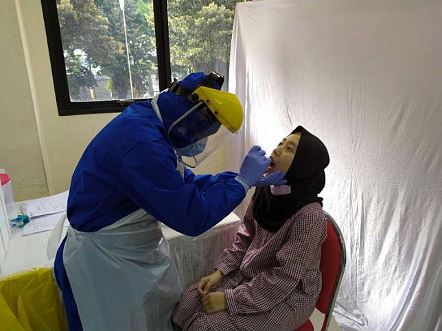 A nurse takes a swab sample from a patient at the Tanah Abang district office in Jakarta on June 21.