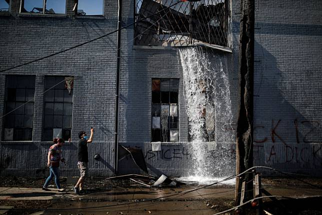 Water gushes out a building that was burnt down during protests last night in the aftermath of a white police officer caught on a bystander's video pressing his knee into the neck of African-American man George Floyd, who later died at a hospital, in Minneapolis, Minnesota, U.S., May 28, 2020.