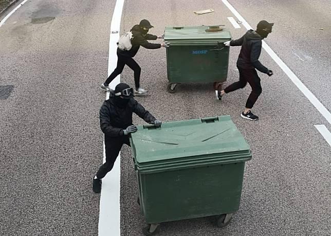 有黑衣人拖出大型垃圾桶堵路。