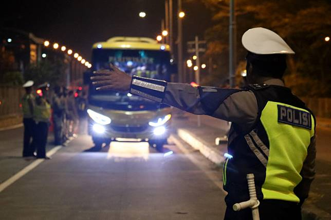 A police officer stops a bus for inspection on Suramadu Bridge on its way to Surabaya from Madura Island in East Java. The inspection was done in anticipation of a mobilization of people to Jakarta ahead of the announcement of the election results on May 22 in Jakarta.