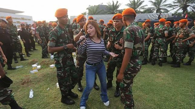Penyanyi dangdut Irma Darmawangsa menghibur anggota TNI-Polri di halaman Gedung DPR RI, Jakarta, Jumat (18/10). [Suara.com/Arya Manggala]