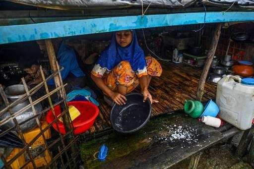หญิงชาวมุสลิมกำลังทำครัวในค่ายที่พักในเมืองเจ้าผิว ในรัฐยะไข่ โดยมีทหารเมียนมาควบคุมเช่นนี้มาหลายปีแล้ว Ye Aung THU / AFP