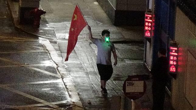 有人手持中國國旗。
