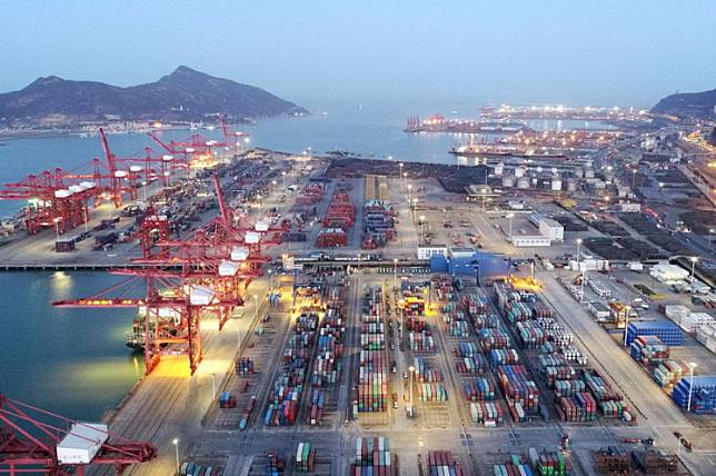 Containers and cargo vessels are seen at sunset at a port in Lianyungang, Jiangsu province, China.