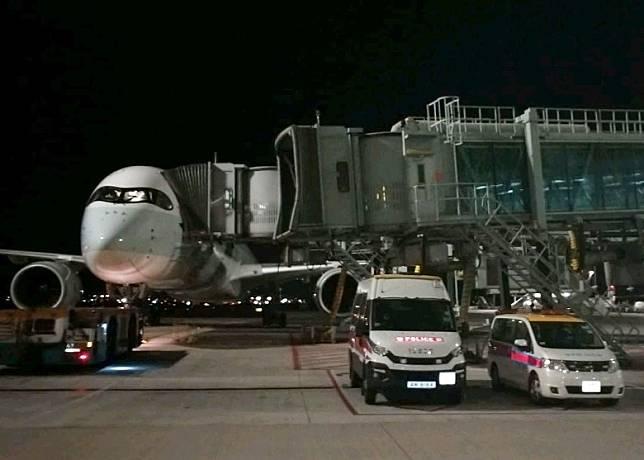 兩輛警車停泊在一架飛機旁。