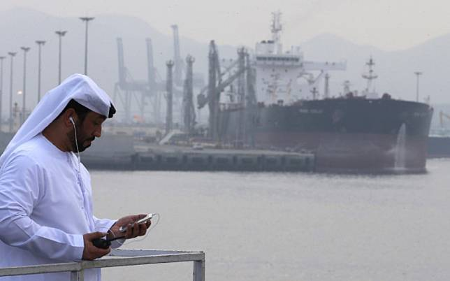 An Emirati man stands at the oil terminal of Fujairah during the inauguration ceremony of a dock for supertankers on Sep. 21, 2016.OPEC fears its record oil cuts will fail to rebalance the market and solve the worst glut in history if a second wave of the COVID-19 pandemic undermines an economic recovery later this year, according to internal OPEC research seen by Reuters.
