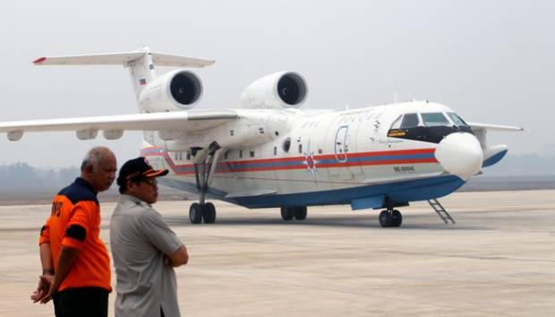 Dua petugas memperhatikan pesawat bom air asal Rusia yang baru mendarat di Bandara Sultan Mahmud Baddarudin (SMB) II, Palembang, Sumsel, 21 Oktober 2015. ANTARA FOTO