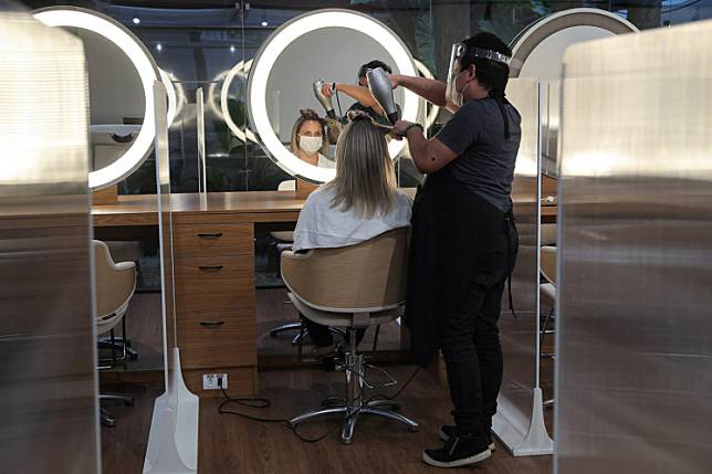 A hairdresser wearing protective mask and face shield uses a hair dryer on a customer's hair between acrylic walls set up for social distancing at a hair salon, as the city eases the restrictions imposed to control the spread of the COVID-19, in Sao Paulo, Brazil July 6, 2020.Two US hair stylists who wore masks while infected with the coronavirus did not pass on COVID-19 to nearly 140 clients they saw over the course of several days, a study said Tuesday.