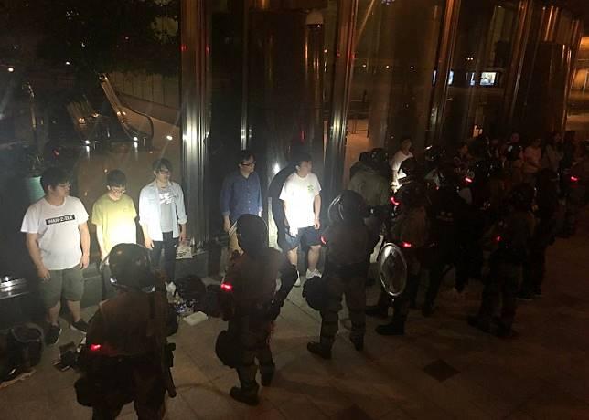 警員在中環長江中心外截查市民。