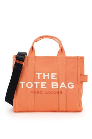 The Small Traveler Tote bag by Marc Jacobs in cotton canvas, featuring adjustable and removable webbing strap, front logo print, back logo patch, zip closure, side handle. Unlined interior with one zip pocket and two small pockets. Steel-finish metalware.