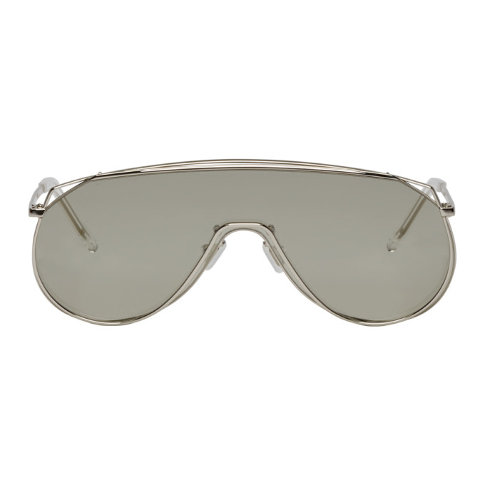 Shield-style stainless steel sunglasses in silver-tone. Single grey lens with 100% UV protection. Sc