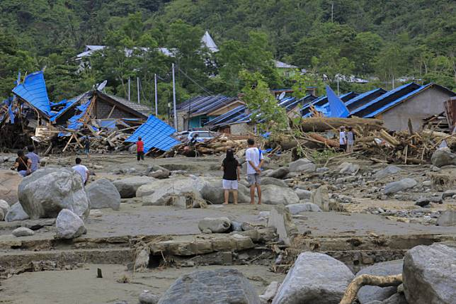 Residents stare at their damaged houses after a flash flood in Sentani, Jayapura regency, Papua, on Sunday, March 17, 2019.