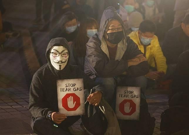 有人手持印上「Stop Tear Gas」紙張。(何天成攝)