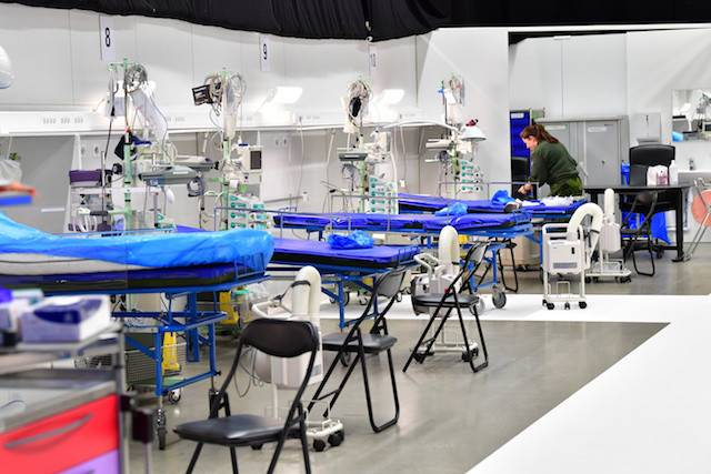 A member of military personnel works to prepare a field hospital which will provide extra intensive care space for patients with COVID-19, inside the exhibition centre Stockholmsmassan in Alvsjo, Stockholm, Sweden on Monday.