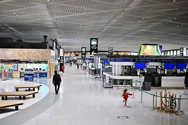 People walk through the departures area at the international terminal at Narita International Airport in Narita, Chiba Prefecture on Tuesday.  Japan's Prime Minister Shinzo Abe declared Tuesday a state of emergency and proposed a stimulus package worth 1 trillion USD as new coronavirus infections spike in Tokyo and elsewhere.