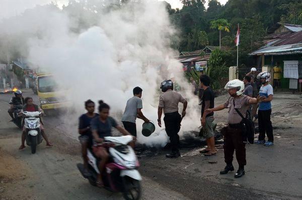 Petugas kepolisian bersama warga membersihkan ban yang dibakar seusai aksi di Jl.Essau Sesa Manokwari, Papua Barat.