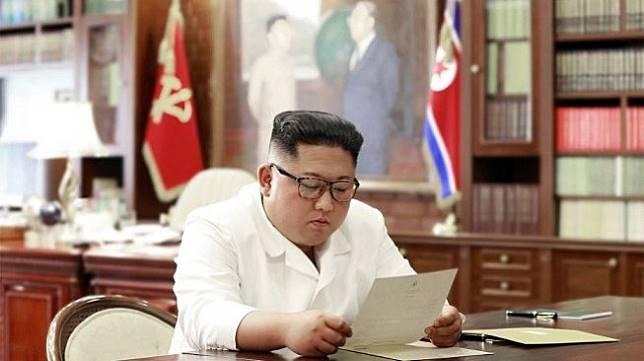 Pemimpin Korea Utara Kim Jong Un membaca surat pribadi. (Foto: KCNA / via AFP)