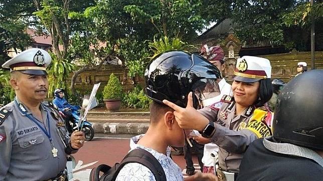 Ilustrasi - Polisi saat memberikan helm kepada pengendara yang menggunakan pakaian ibadah dan tidak menggunakan helm di Tabanan, Bali, Kamis (2/5/2019).