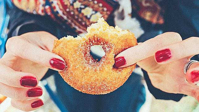 Ilustrasi wanita makan makanan manis. Unsplash/Thomas Kelley