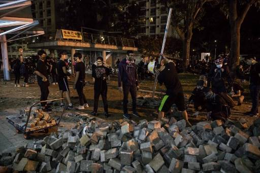 Protesters dig up paving bricks outside the MTR train station at the Chinese University of Hong Kong (CUHK) in Hong Kong on November 12, 2019. Hong Kong pro-democracy protesters fought intense battles with riot police on a university campus and paralysed the city's upmarket business district Tuesday, extending one of the most violent stretches of unrest seen in more than five months of political chaos.