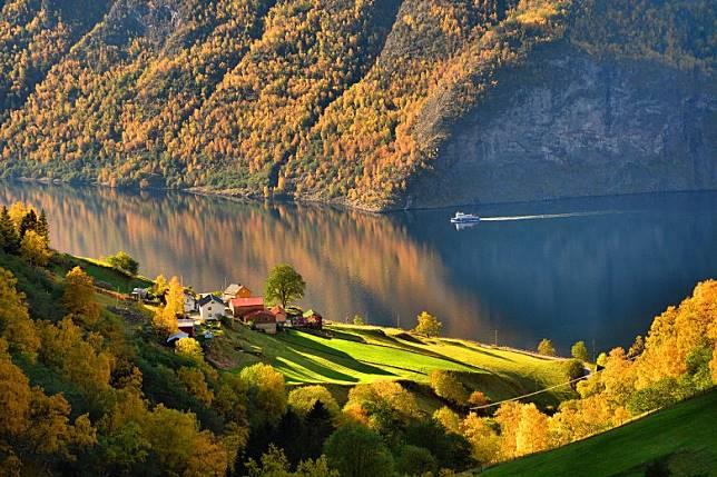 挪威松恩峽灣的秋色倒映於河上,跟森林、小屋、飛瀑與溪流共構出如畫風景。(互聯網)