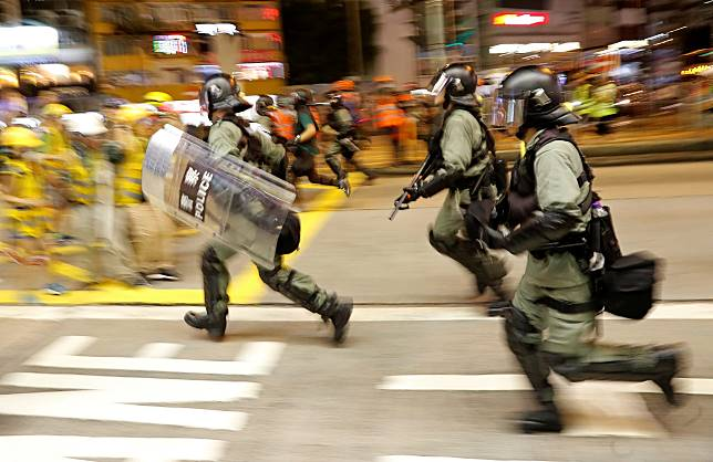 Riot police advance during a protest near Mong Kok police station in Hong Kong