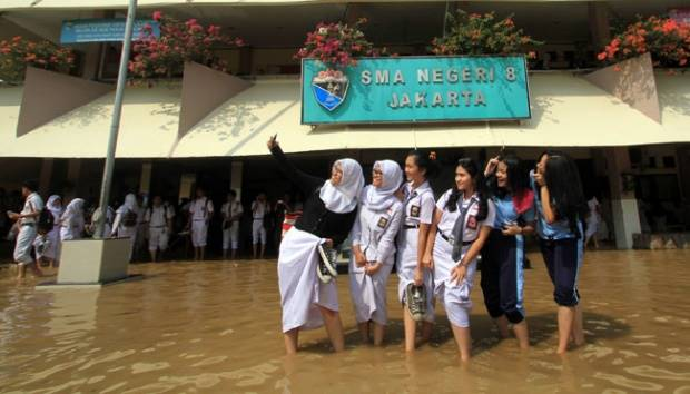 Sejumlah murid berfoto selfie saat banjir menggenangi sekolah mereka di SMA Negeri 8, Bukit Duri, Jakarta, 16 November 2015. Sungai Ciliwung meluap dan menggenangi sekolah hingga setinggi 50 cm. TEMPO/Eko Siswono Toyudho