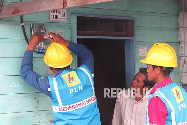 Petugas PLN memasang meteran listrik di sebuah rumah warga di Desa Sabang Mawang Balai, Kecamatan Pulau Tiga, Natuna, Kepri.
