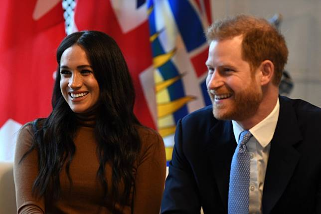 Britain's Prince Harry, Duke of Sussex and Meghan, Duchess of Sussex, gesture during their visit to Canada House in thanks for the warm Canadian hospitality and support they received during their recent stay in Canada, in London on January 7, 2020.