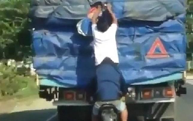 Bajing loncat membongkar barang bawaan sebuah truk.