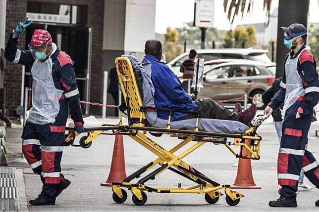 An emergency paramedic wearing full COVID-19 coronavirus personal protective equipment (PPE) flashes the victory sign as they arrive with a patient at the Greenacres Hospital in Port Elizabeth, South Africa, on Friday.