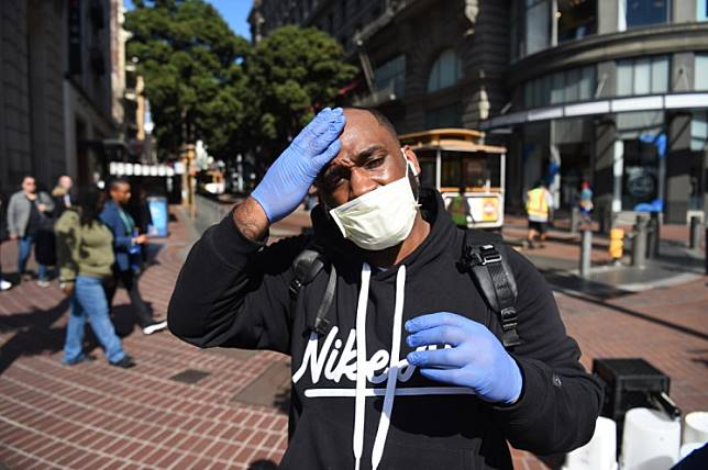 Cameron Nightingale adjusts his mask and gloves, a precaution to protect himself from  coronavirus, while walking by cable car in San Francisco, California on Feb. 27, 2020. US health officials on Friday reported a third case of the new coronavirus transmitted to a person who did not travel overseas or come in contact with anyone known to be ill, indicating the disease was spreading in the country.