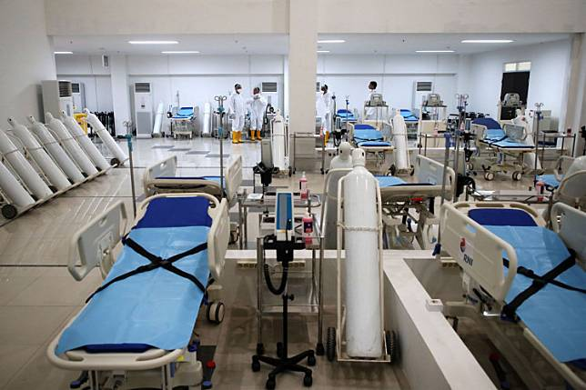 Medical workers arrange hospital beds at a COVID-19 hospital in the Wisma Atlet Kemayoran apartment complex in Jakarta on March 23. The hospital can accommodate up to 3,000 patients. Antara/Kompas/Heru Sri Kumoro/Pool