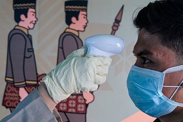A person checks the temperature of a passenger (right) wearing a facemask to help stop the spread of a deadly virus that began in the Chinese city of Wuhan, as he arrives at the Sultan Mahmud Badaruddin II International airport in Palembang on Jan. 26.