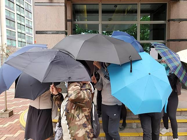 24歲被告鄧力豪被傘陣包圍。  葉君怡攝