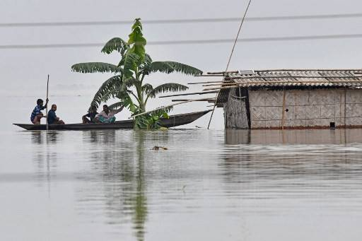 Villagers paddle their boat next to a partially submerged hut in the flood affected area of Hatishila, in Kamrup district of Assam state on July 14, 2020. - Flooding is an annual phenomenon in India's northeast, claiming hundreds of lives each year.