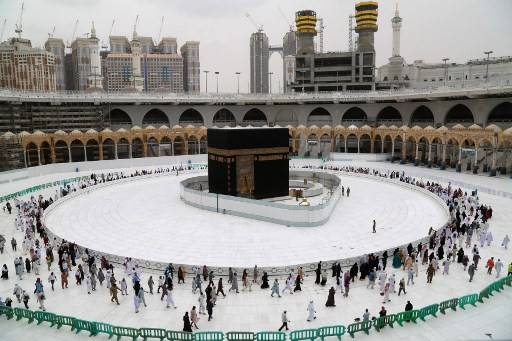 Muslim worshippers circumambulate the sacred Kaaba in Mecca's Grand Mosque, Islam's holiest site, on March 13, 2020.Saudi Arabia on Thursday extended curfew restrictions on Islam's two holiest cities to 24 hours to stem the spread of coronavirus
