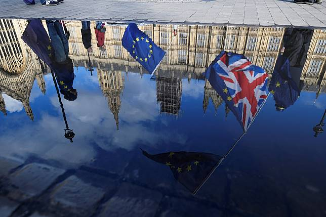 FILE PHOTO: Anti-Brexit demonstrators waving EU and Union flags are reflected in a puddle in front of the Houses of Parliament in London
