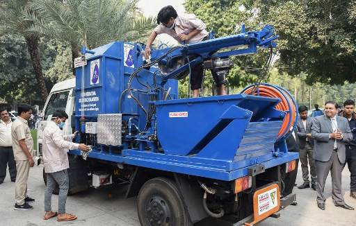 Indian workers scrub a sewer cleaning machine on a truck before its unveiling during an event to celebrate World Toilet Day in New Delhi on November 19, 2018. Hundreds of