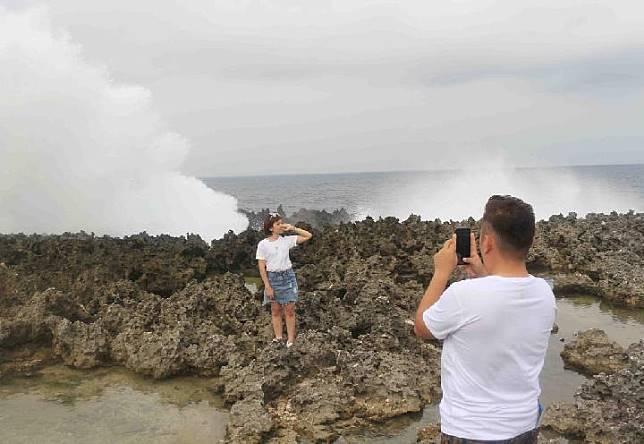 Wisatawan berfoto dengan latar belakang ombak menghempas karang di objek wisata Water Blow, Nusa Dua, Bali. Wisatawan tidak akan bisa menikmati objek ini secara gratis karena bakal dikenakan retribusi. TEMPO | Made Argawa.