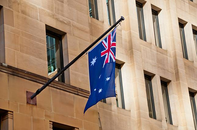 Flag of Australia hang from a sandstone building.