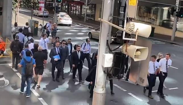 高雲翔在律師團和工作人員陪同下過馬路前往法庭。